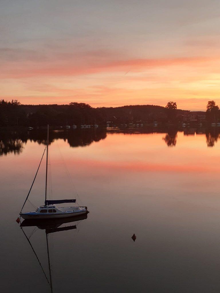 Zachód słońca nad jeziorem. Na jeziorze odbija się w tafli wody las oraz pomarańczowe niebo. Jedna łódka na wodzie.