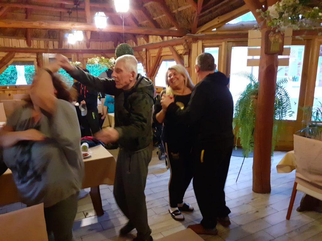 Grupa osób tańcząca w drewnianej restauracji
