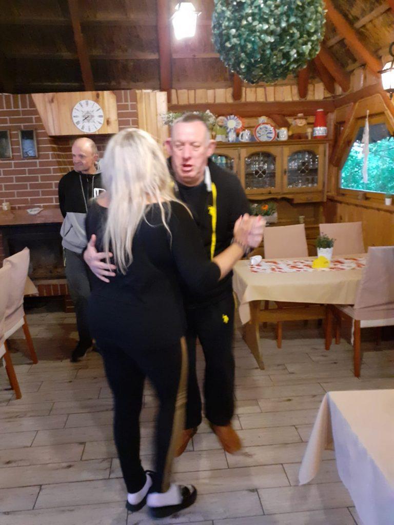 Mężczyzna tańczy z kobietą. Para tańczy między stołami