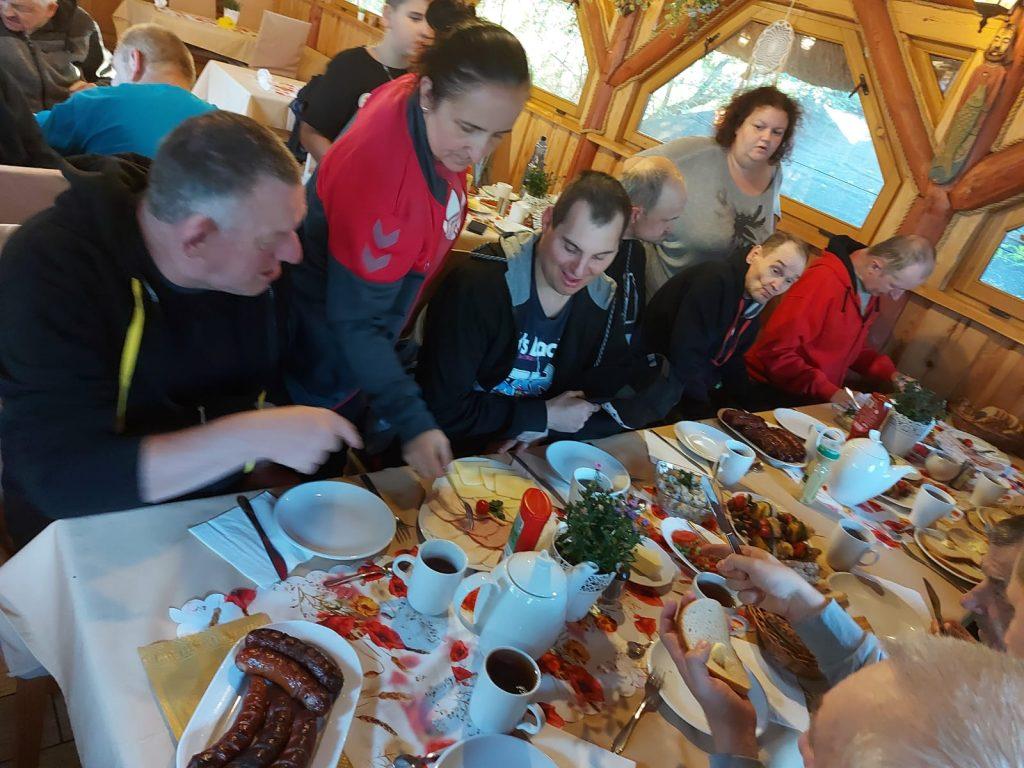 Mieszkańcy siedzący przy stołach zastawionych jedzeniem. Na stołach kiełbasy, chleb, sery, wędliny itd. Nad mieszkańcami opiekunki