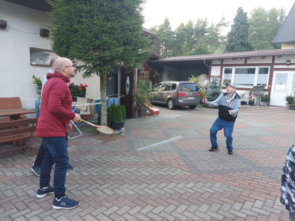 Mieszkaniec grający w badmintona z opiekunem