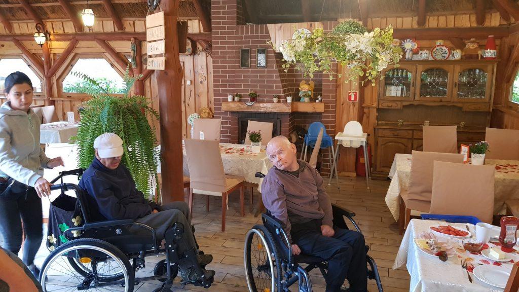 Dwóch mężczyzn na wózkach, przy jednym stoi opiekun w tle drewniana witrynka, stoły oraz obrusy na stołach (wnętrze restauracji)