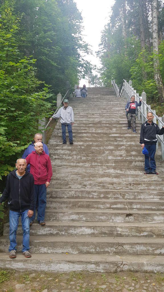 Szerokie duże betonowe schody, a na nich grupa mieszkańców, która schodzi w dół. Pomiędzy schodami drzewa