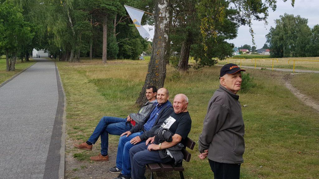 Podopieczni odpoczywają na ławce, przed nimi długi chodnik, a za ławką Pas zieleni. Jeden mężczyzna stoi i patrzy w dal.