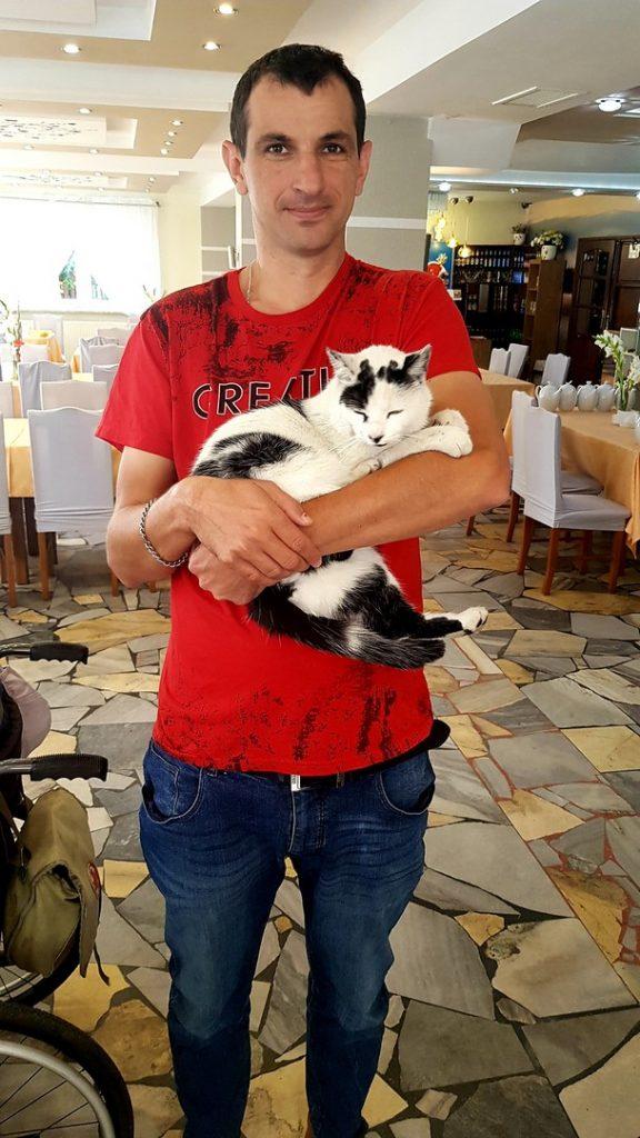 Mężczyzna trzyma na ręku biało-czarnego kota. W tle restauracja, stoły oraz bar.