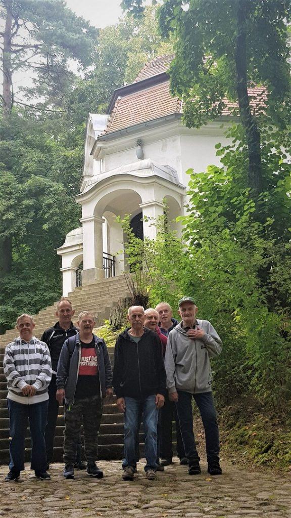 Siedmiu mężczyzn stoi przed schodami kapliczki, obok niej zielone drzewa