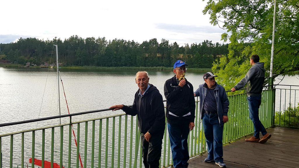 Czterech mężczyzn stoi na drewnianym tarasie i opiera się o metalową balustradę. Jeden z nich patrzy w stronę jeziora. Z tyłu las i duża łódka.