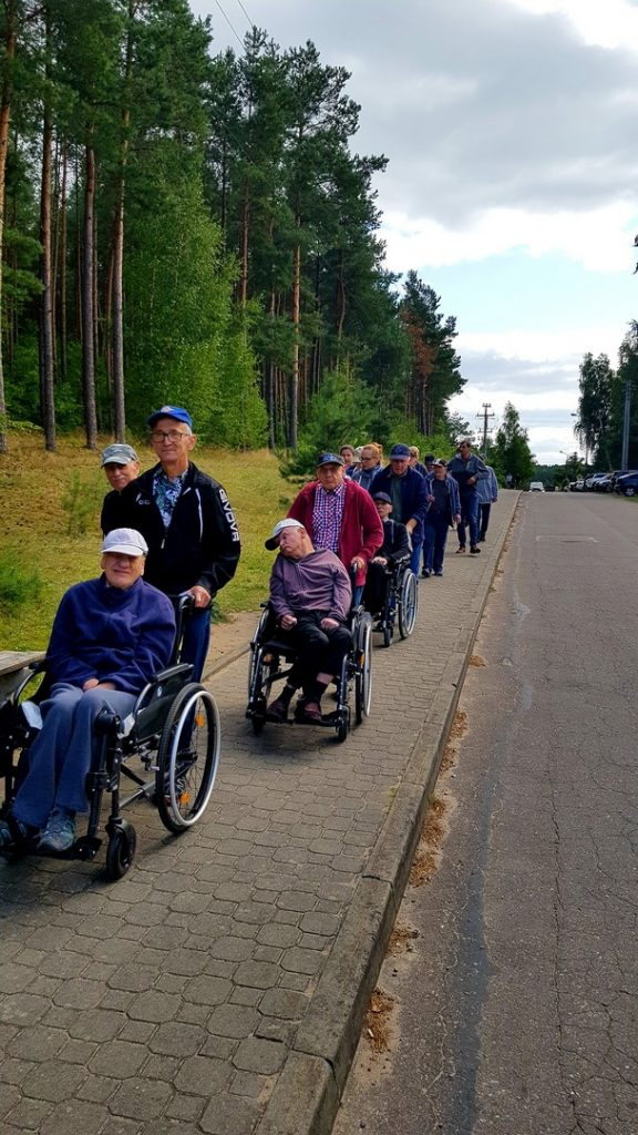 Podopieczni podczas spaceru idą chodnikiem. Trzy pierwsze osoby pchają wózki z siedzącymi na nich mieszkańcami. Wszyscy idą gęsiego.