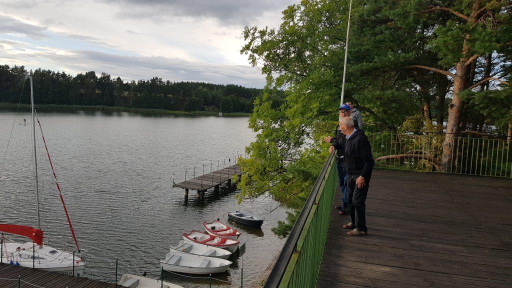 Trzech mężczyzn stoi na drewnianym tarasie, na dole łódki, jezioro oraz dwa pomosty