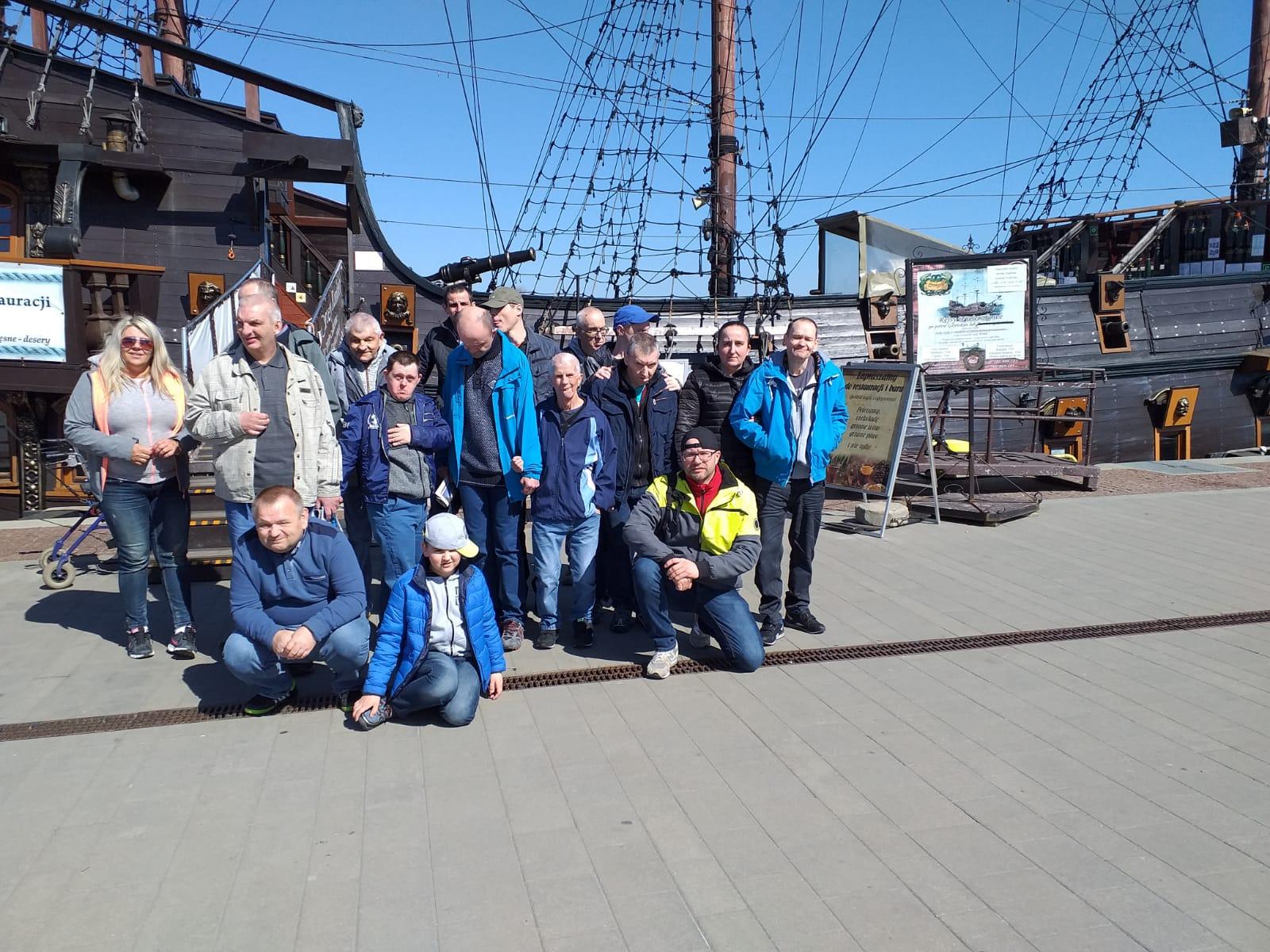 Grupa osób pozuje na tle dużego statku z żaglami