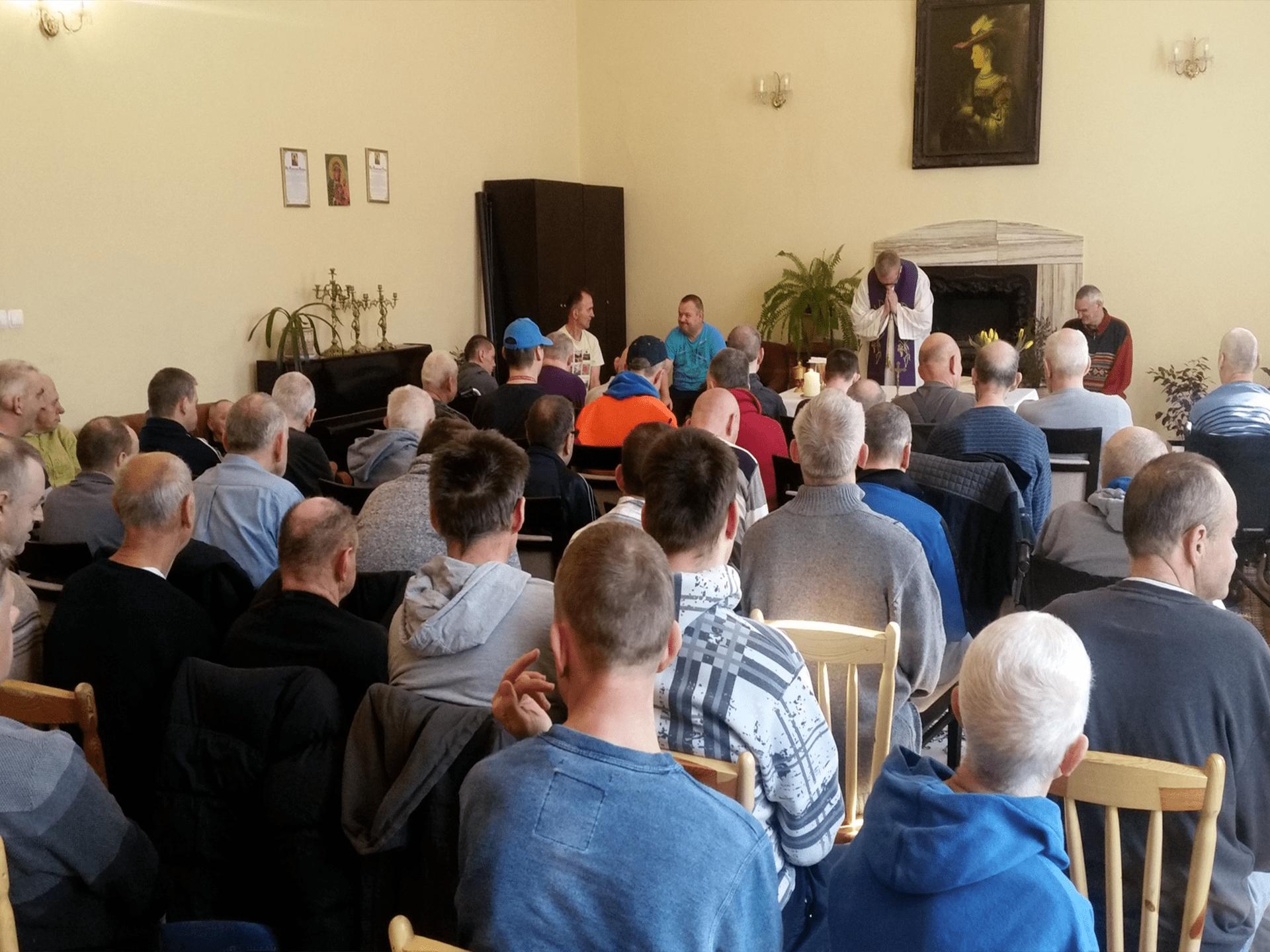 Grupa mieszkańców siedzących na dużej sali, słuchających mszy. Przed nimi ksiądz, który prowadzi Mszę Świętą.