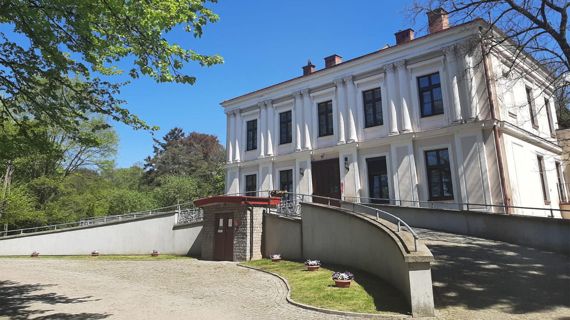 Bezchmurne niebo, biały pałac posiadający 9 okien na froncie oraz podjazd pod same drzwi z obu stron.
