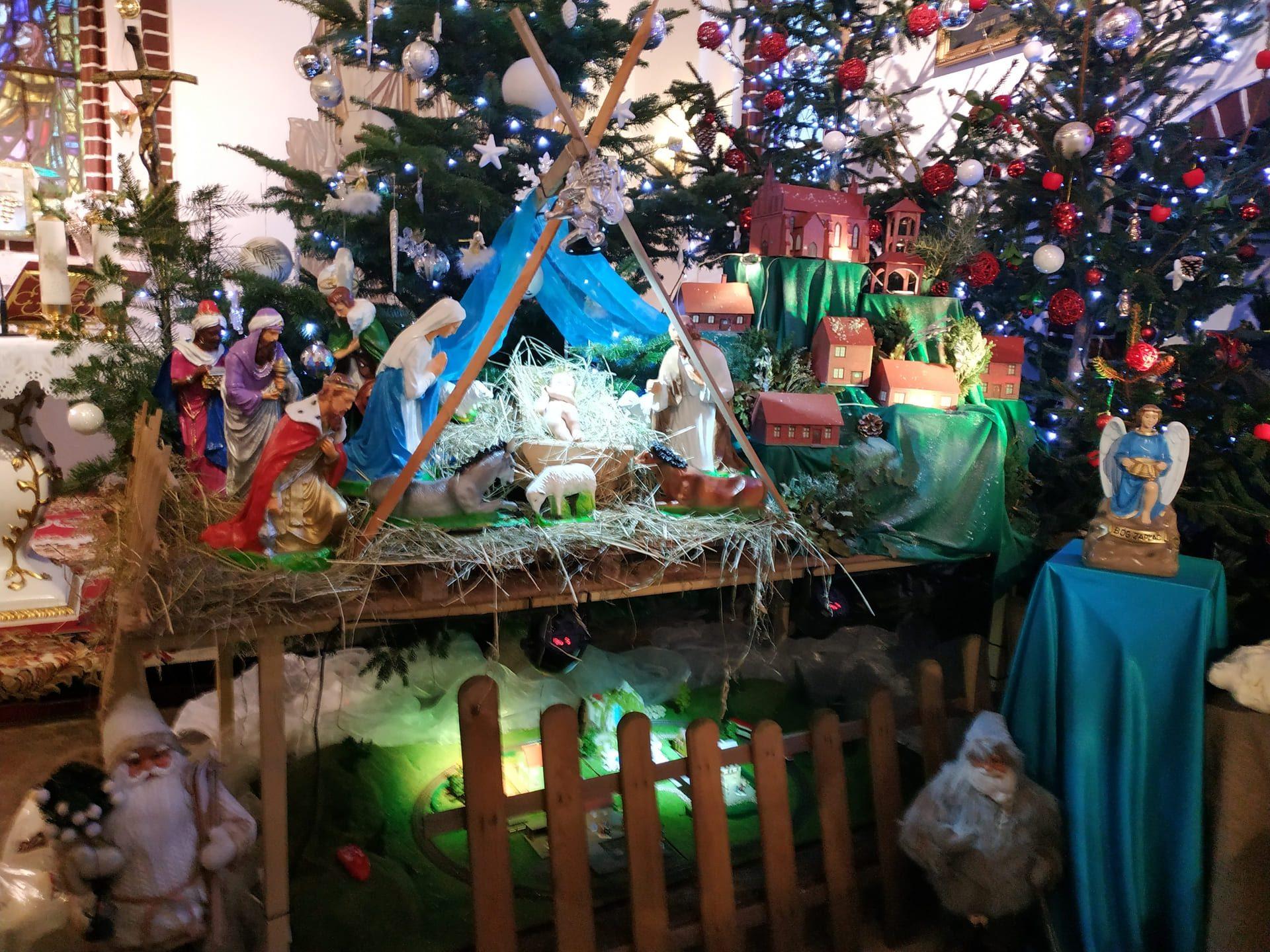 Kolorowa szopka Bożonarodzeniowa, w tle choinka i bombki