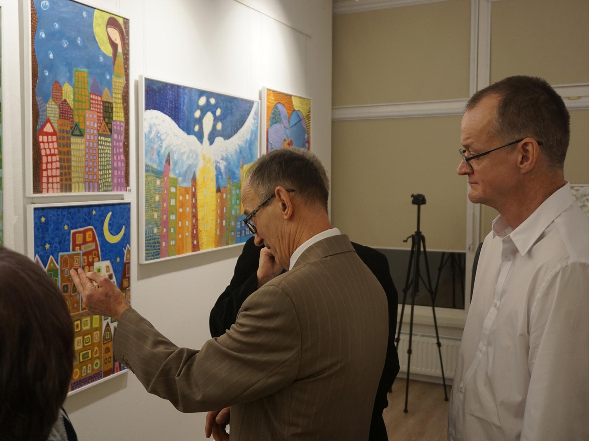 Zainteresowane osoby podczas oglądania kolorowych obrazów podczas wernisażu Rokocińskie Anioły