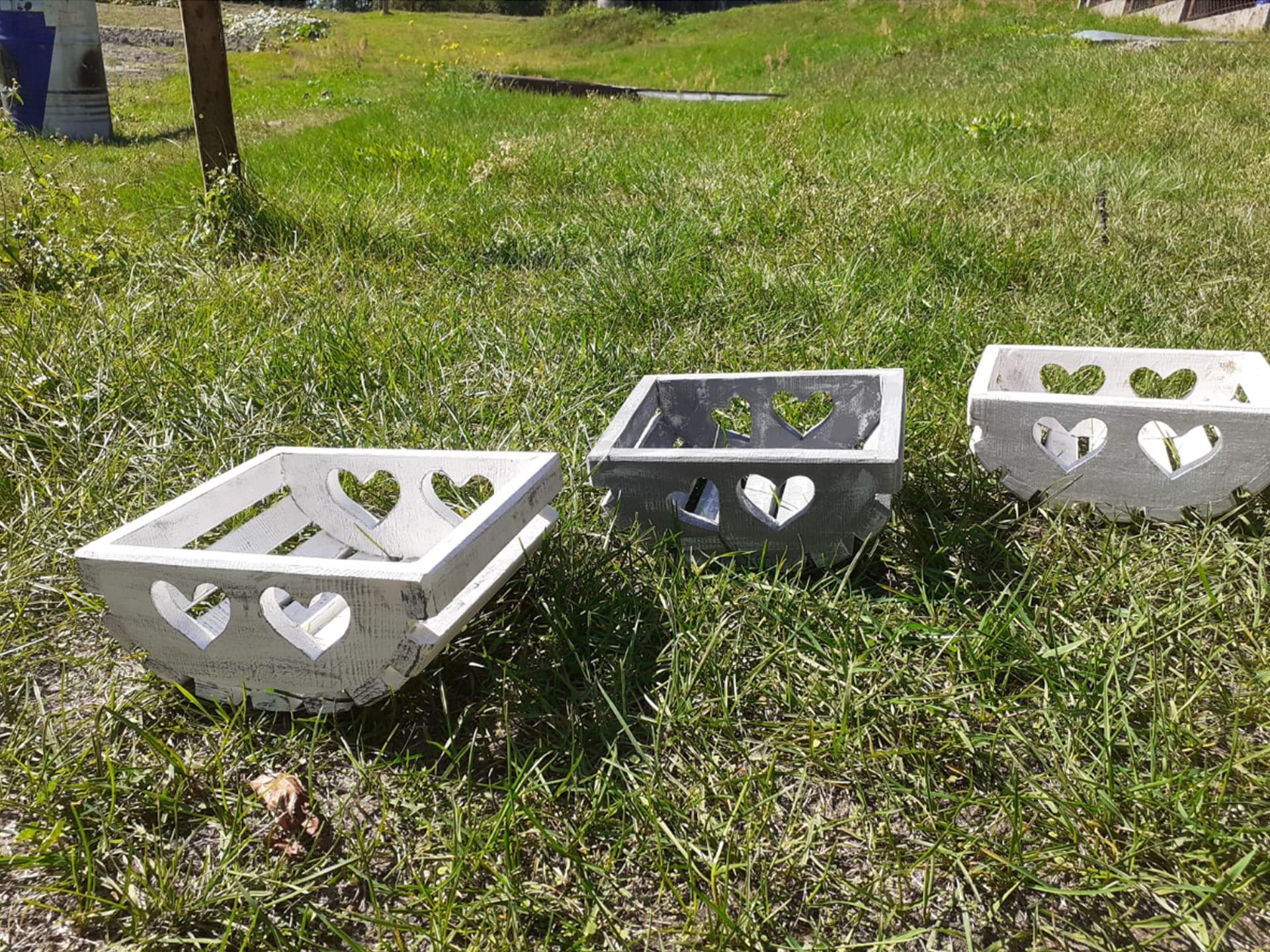 Trzy drewniane skrzynki leżą na trawie. Ozdobione są wyciętymi sercami w drewnie.