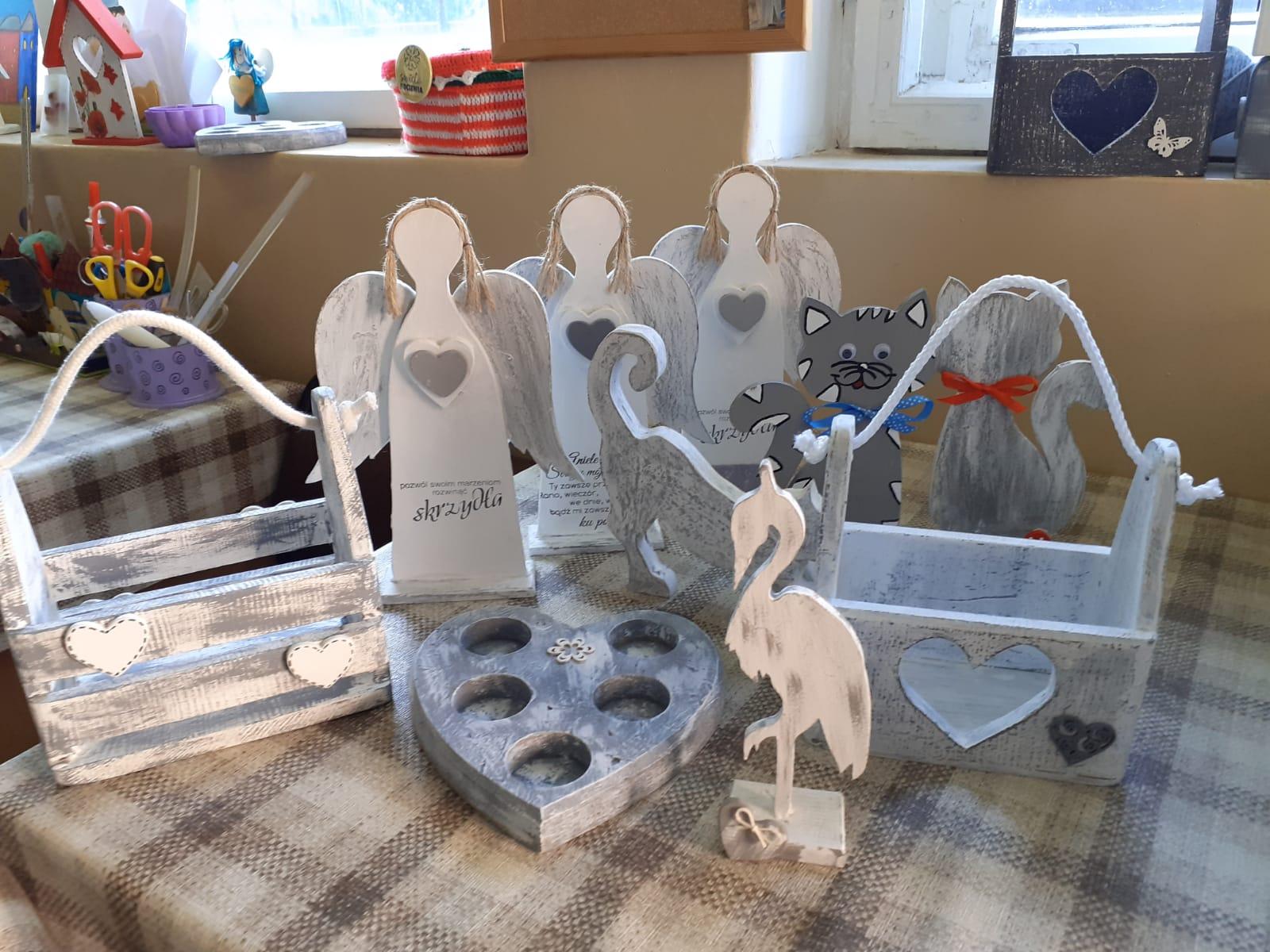 Zbiór drewnianych ozdób pomalowanych na kolor biało-szary. Aniołki, świecznik, dwie szkatułki i figurki kotów
