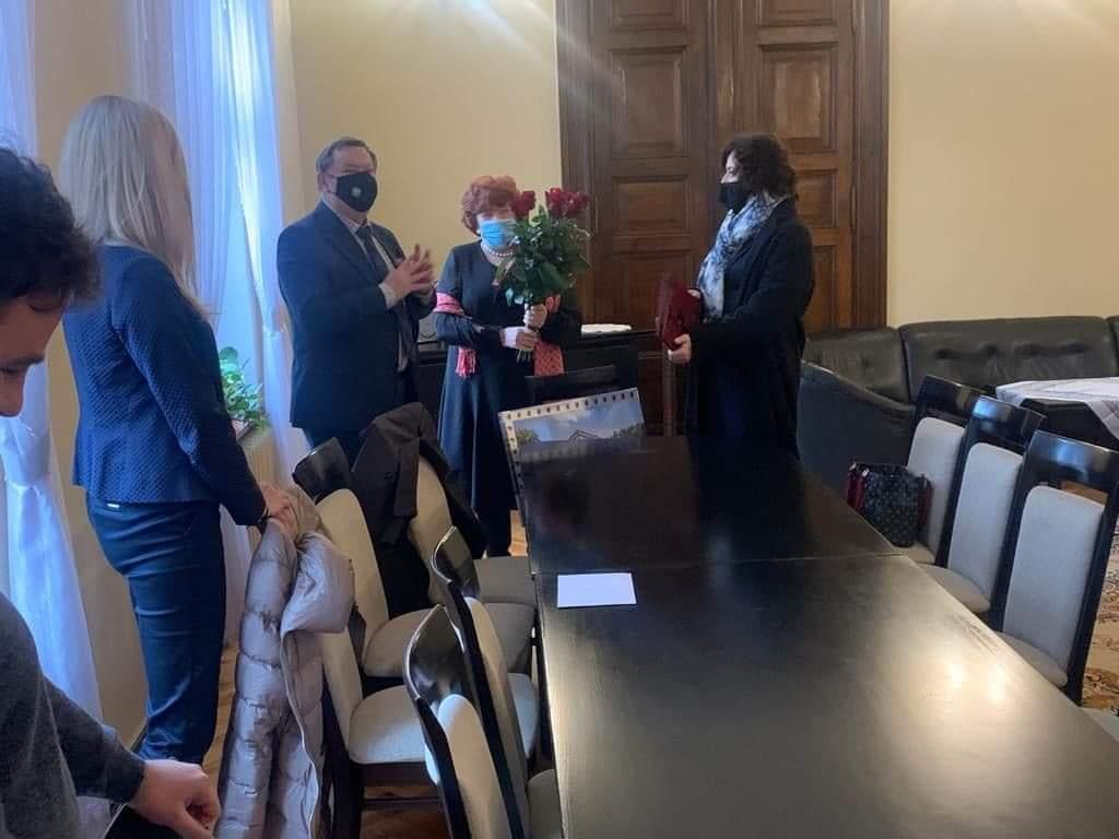 Starosta oraz członek zarządu wręczają upominek oraz kwiaty p. Dyrektor. Obok nich stoją pracownicy.