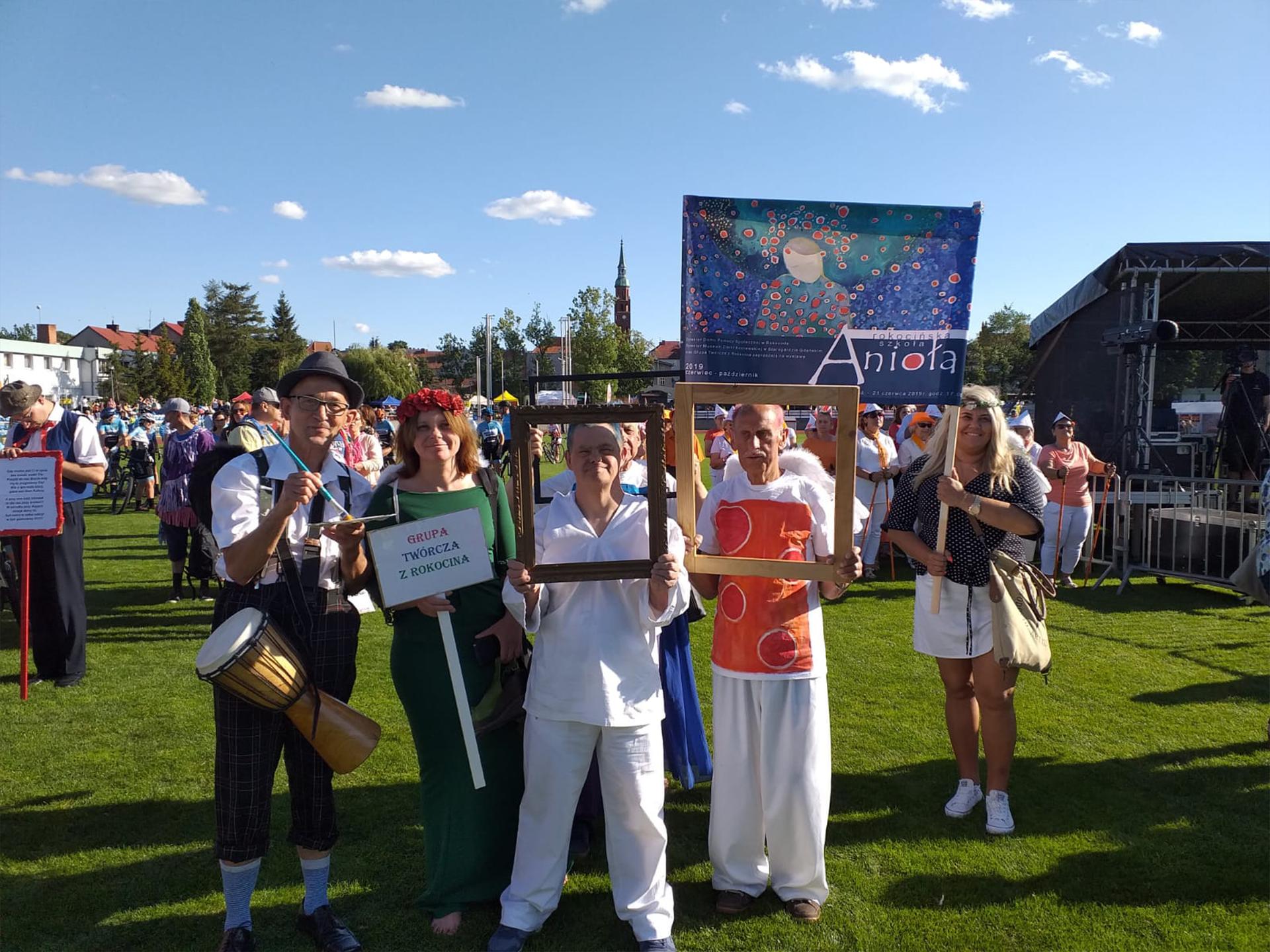 Grupa osób ubrana w Anioły promuje nadchodzący wernisaż, w tle kobiety trzymające transparent, z przodu podopieczni trzymający ramki od obrazów