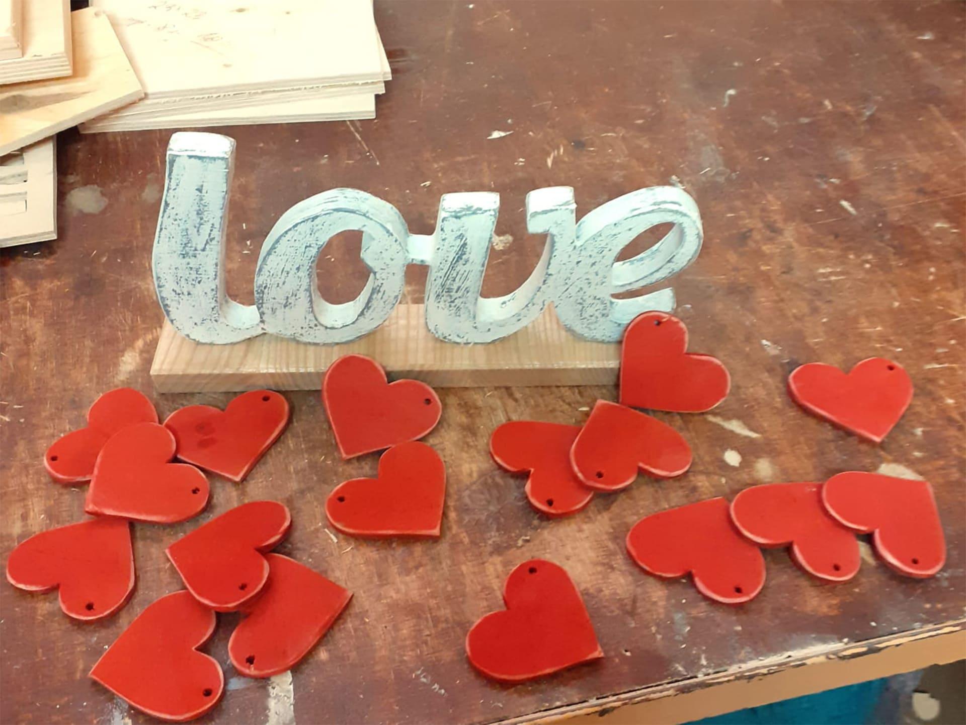 Szary napis z drewna Love na przy nim 17 czerwonych serc z drewna leżących na stole