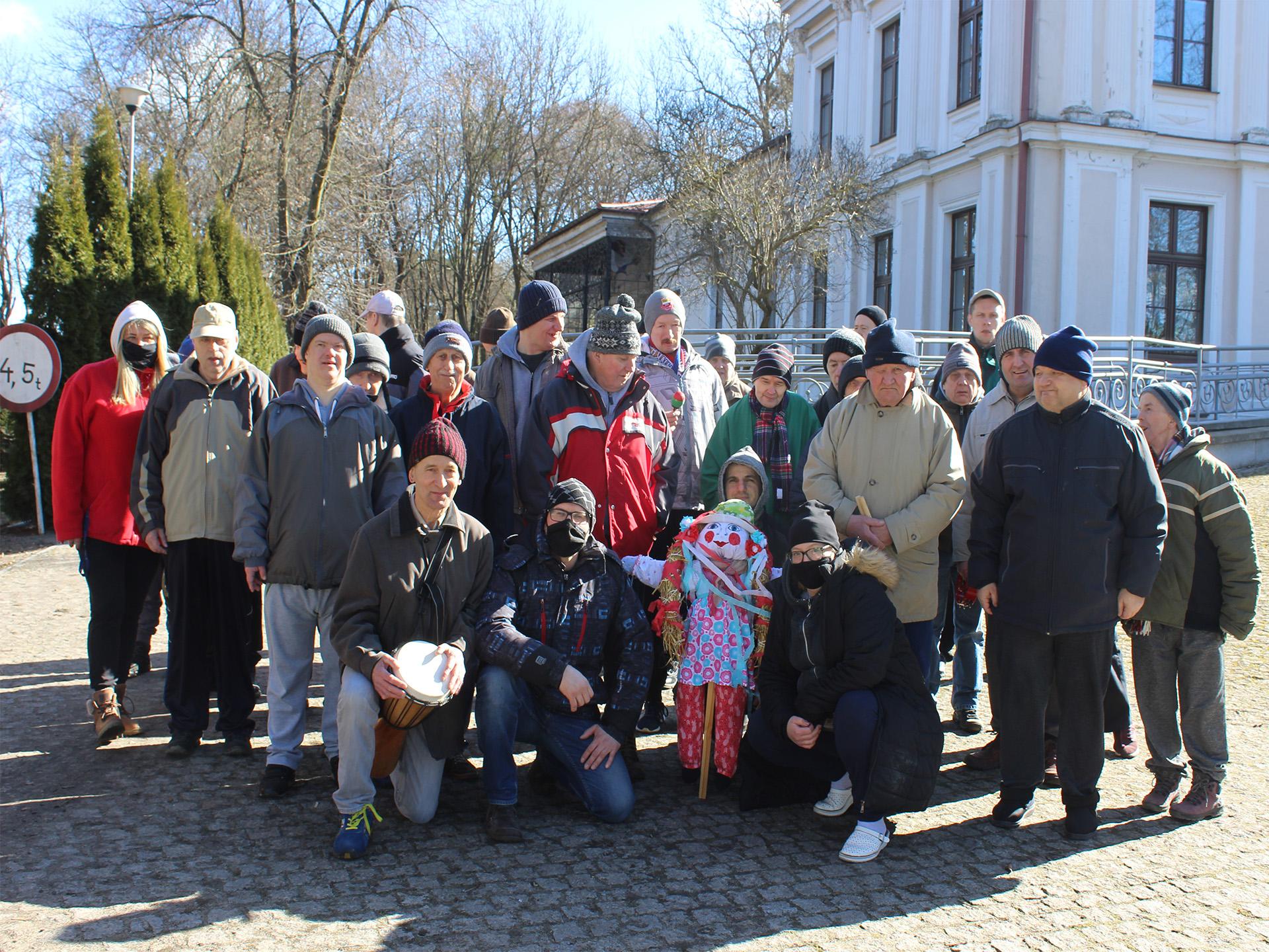 Grupa mieszkańców stojąca na betonowej kostce.