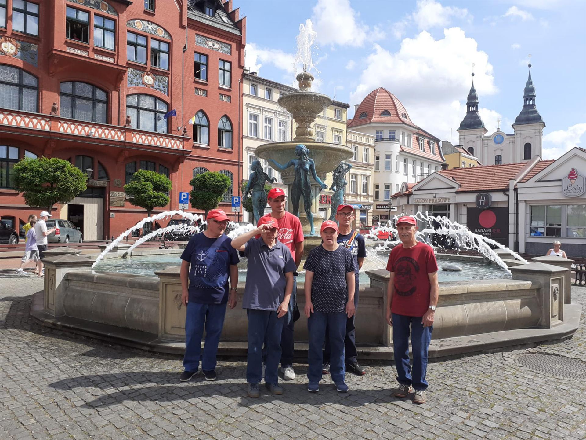 Sześciu mieszkańców stoi przy fontannie na rynku w Chojnicach. W tle piękne stare wysokie kamienice