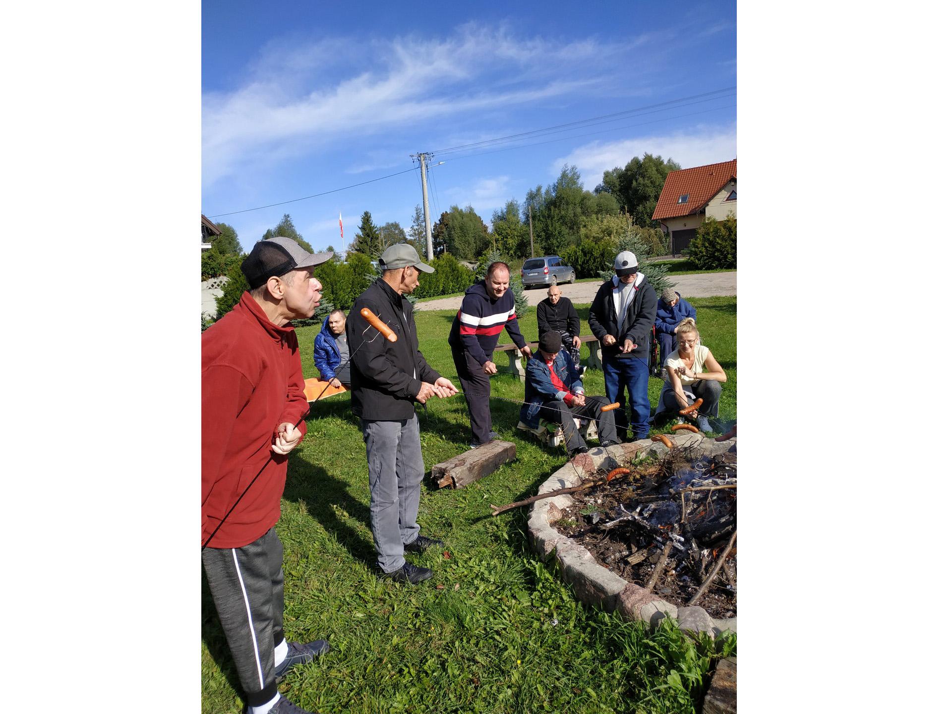 Grupa osób stojących nad ogniskiem przygotowuje sobie kiełbaski nabite na kije