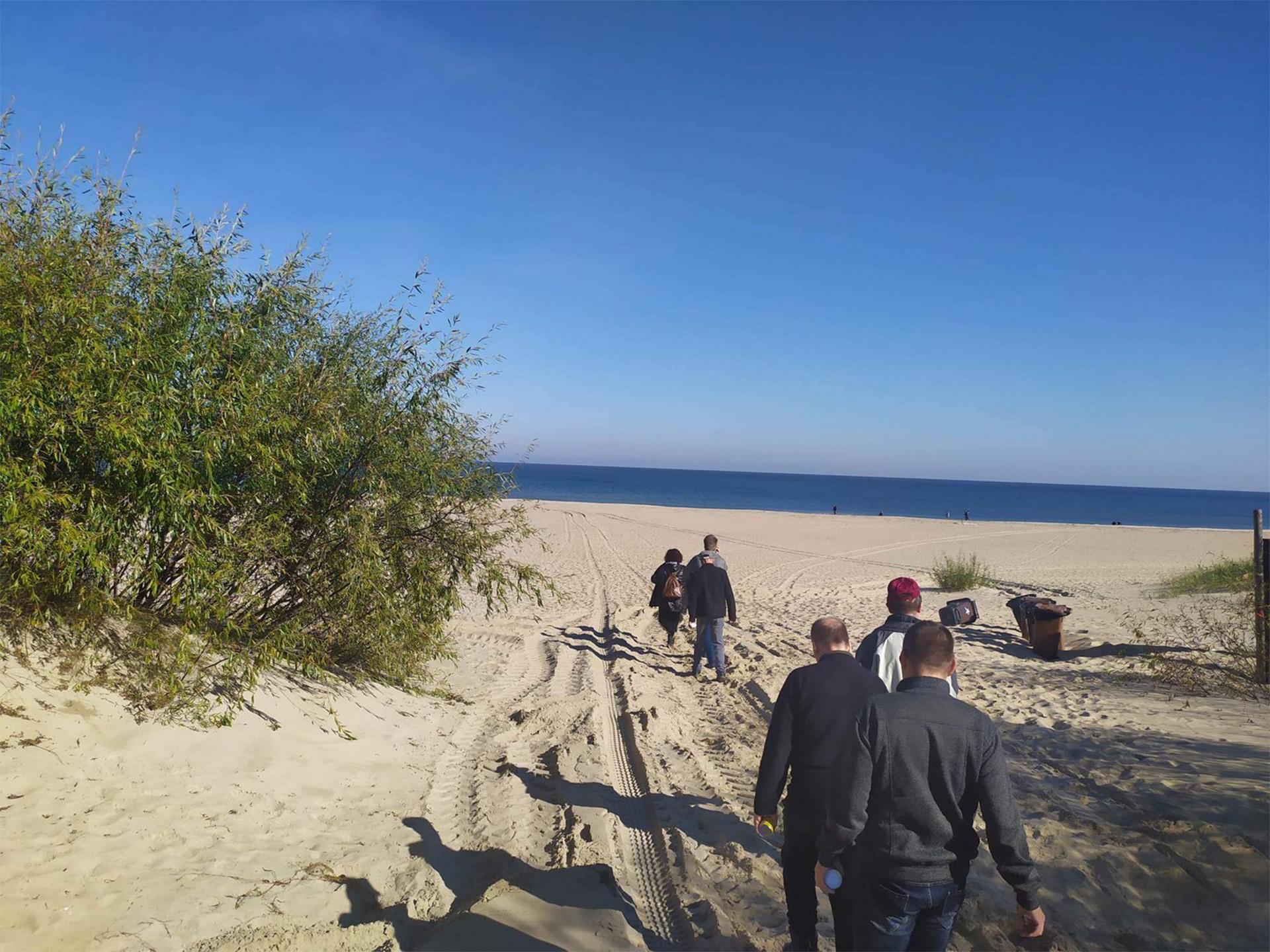 Mieszkańcy wchodzą na plażę, idą po złotym piasku przed nimi bezchmurne niebieskie niebo oraz morze